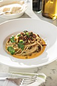 Spaghetti with Chanterelles and Black Truffle over Butternut Squash Purée in white wide-rimmed bowl