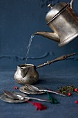 Making tea with a silver teapot