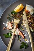 Zucchini-Fritters mit Lachs und pochiertem Ei: Essensreste auf Teller