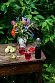 Currant syrup and currant lemonade on a summer table in a garden