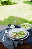 Ofengebackene Hühnerbrust mit Pesto-Nudeln auf Tisch im Garten