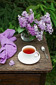 A cup of tea and a lilac blossom bouquet on a table outdoors