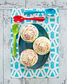Cupcakes with buttercream and colourful sugar sprinkles (top view)