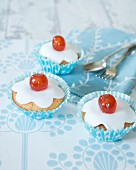 Cupcakes decorated with icing and glace cherries