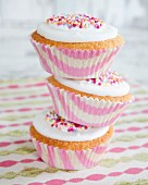 Three stacked cupcakes decorated with icing and colourful sugar sprinkles