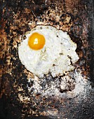 A fried egg on a rusty metal plate (top view)