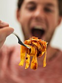 A man holding a fork with tagliatelle bolognese
