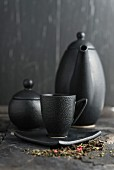 Tea in a black cup in front of a teapot and sugar pot