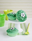 Green cupcakes decorated with footballs and grass