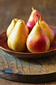 Yellow and red pears on a wooden plate