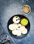 Traditional breakfast with Idli (rice cakes), coriander chutney, coconut chutney and coffee (South India)