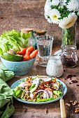 Salad with carrots, walnuts, avocado, onions and roast chicken