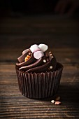 A chocolate cupcake topped with mini marshmallows and toffee sprinkles