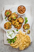 Spicy courgette fritters with mint, cucumber raita, apricot chutney, flatbread and coriander leaves