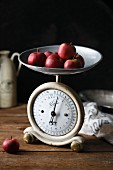 Several small red apples on an old kitchen scale