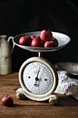 Mehrere kleine rote Äpfel auf alter Küchenwaage