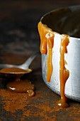 Caramel sauce dripping from a saucepan