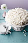 A cake covered with cream cheese and coconut flakes on a white cake stand