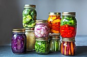 Stacked preserving jars of freshly pickled vegetables in front of a grey background