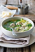 Clear broth with dumplings, noodles and vegetables