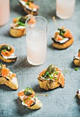 Crostini with smoked salmon, pesto sauce, watercress and capers and pink grapefruit cocktails