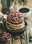 Sweet breakfast with pancakes with fresh forest berries and honey in cast iron pan over rustic wooden background