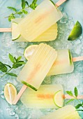 Summer refreshing lemonade popsicles with lime and mint with chipped ice over blue background
