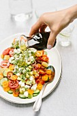A woman is pouring balsamic salad dressing onto the salad