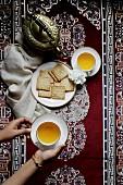 Grüner Tee in Kanne und Tassen serviert mit Gebäck (Aufsicht)