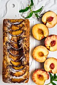 A loaf-shaped peach bread topped with cinnamon and brown sugar on a marble board