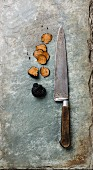 Sliced Black truffle and kitchen knife on stone shale slate background