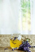 Organic raw honey in glass jar flavored with lavender flowers, standing on table with sackcloth