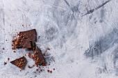 Grob gehackte dunkle Schokolade bestreut mit Kakaopulver auf grauem Untergrund