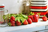 Fresh strawberries, melissa and empty metal jars