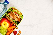 Healthy school lunch box with sandwich, apple, grape, carrot and bottle of water close up on white wooden background