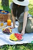 Junge Frau sitzt auf Picknickdecke im Park und isst Wassermelone