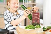 A girl grating zucchini