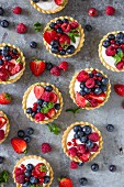 Mini tarts with vanilla cream and summer fruits seen from above