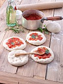 Unbaked pizzas with tomato sauce