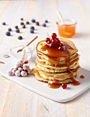 Stacked pancakes with syrup and berries