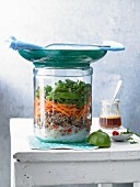 Glass noodle salad with beef mince and coriander in a glass jar