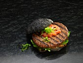 A grilled hamburger on a black bread roll