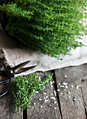 Fresh thyme and salt on a wooden background