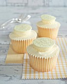 Cupcakes with cream and white chocolate disks