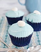 Cupcakes with blue cream frosting and a fondant shell on the top
