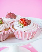 Cupcakes with strawberry frosting and a fresh strawberry