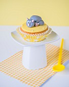 A cupcake with a fondant icing cat and mouse on the top