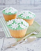 Cupcakes with green buttercream and white sugar flowers