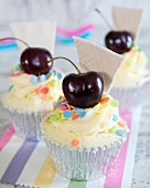 Cupcakes with sugar confetti and a cherry