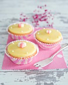 Cupcakes with yellow fondant icing and cubes